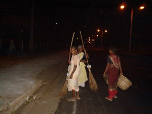 Limpeza de vias públicas realizada por mulheres durante a madrugada com vassouras de palha