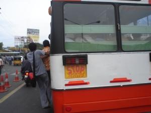 Homens correm para pegar o ônibus e na maioria ficam para fora pela quantidade de pessoas.